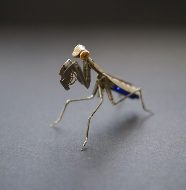 Close up of a praying mantis insect replica made of clockwork parts.