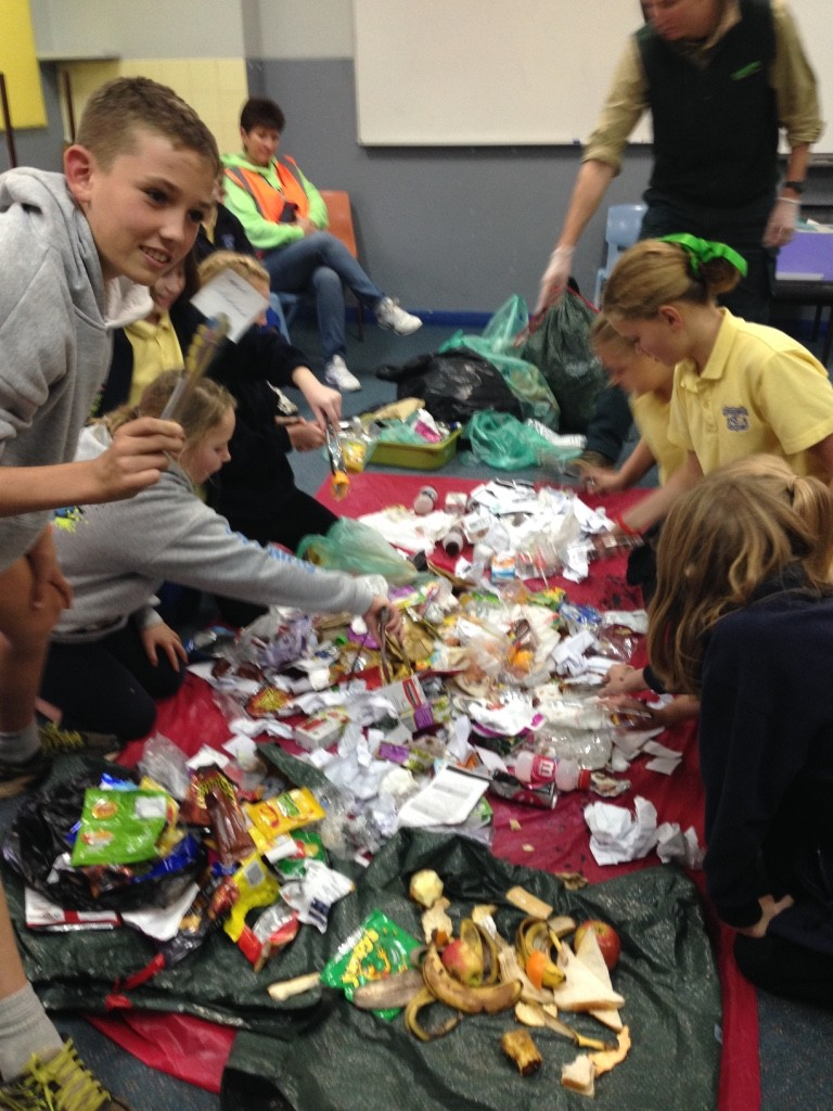 Students using metal tongs to sort the waste they collected at their school.